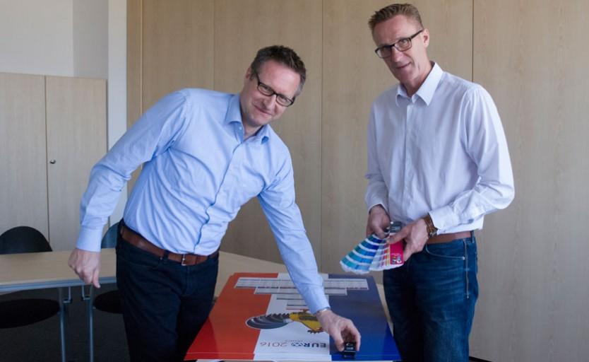Карстен Зольцер и Роланд Шредер изучают график матчей UEFA Euro 2016, отпечатанный новыми УФ-красками