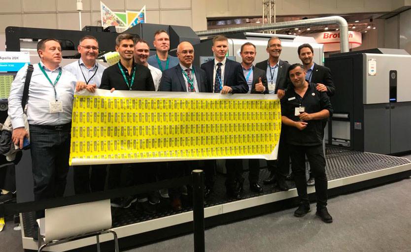 Объединённая команда специалистов компаний-участников с тестовым отпечатком на фоне  ЦПМ HP Indigo 20000